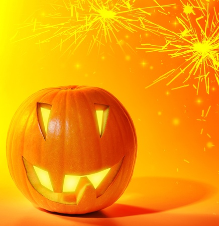 Halloween glowing pumpkins over bright yellow fireworks background, autumn holiday traditional party decoration, fun concept photo