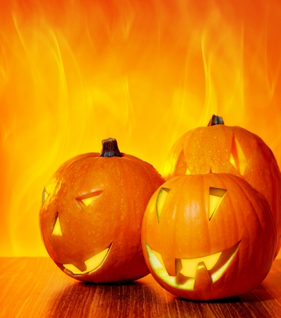 pumpkin head: Halloween glowing pumpkins over bright fire yellow background, with copy space, autumn holiday traditional party decoration, fun concept
