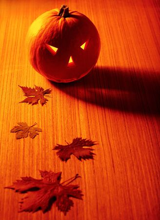 Halloween glowing pumpkin with leaves over warm wooden background, autumn holiday, traditional party decoration, fun concept photo