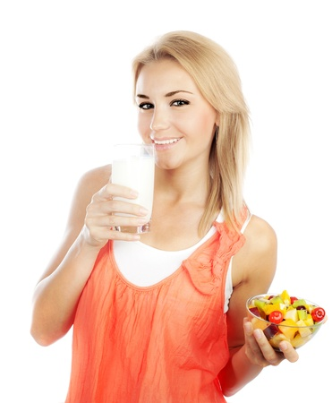 woman drinking milk: Pretty girl eating fruit salad and drinking milk, healthy fresh breakfast, dieting and health care concept Stock Photo