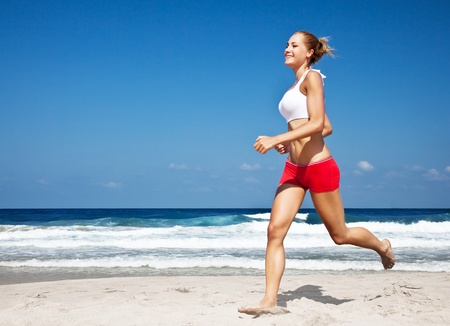 Healthy woman running on the beach, doing sport outdoor, freedom, vacation, heath care concept with copy space over natural blue background photo