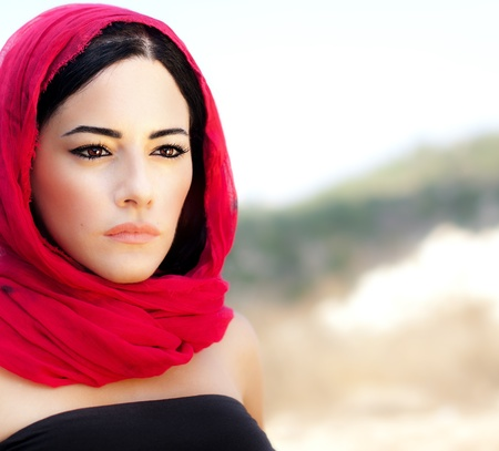 Beautiful arabic woman wearing red scarf, traditional muslim clothes, latest fashion design, stylish female portrait over soft natural background with copy space photo
