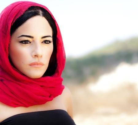 middle eastern clothing: Bella donna araba indossa sciarpa rossa, abiti tradizionali musulmani, ultima moda design, elegante ritratto femminile su fondo morbido naturale con copia spazio Archivio Fotografico
