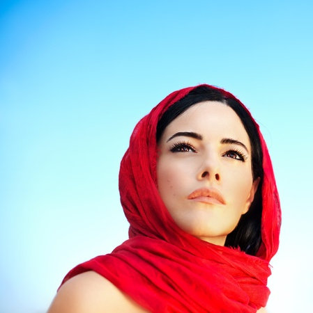 Beautiful arabic woman wearing red scarf, traditional muslim clothes, latest fashion design, stylish female portrait over blue natural background with copy space, soft focus photo