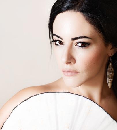 Bella modelo morena con ventilador chino, closeup retrato femenino aislado en el fondo beige