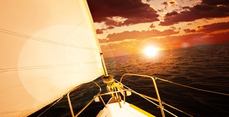 Romantic sunset and sail boat, dramatic sky with red clouds and sun flare over calm sea, water sport, travel and freedom concept photo