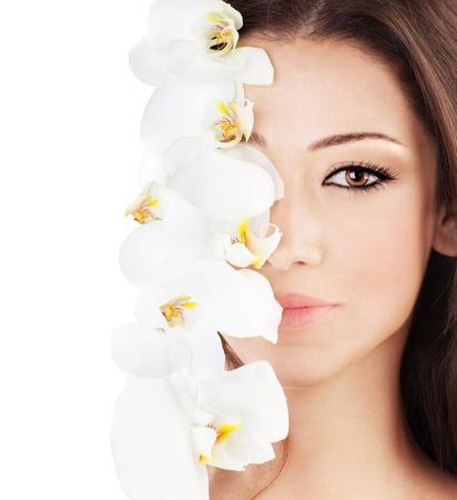 Gros plan sur le beau visage avec orchidée blanche fleur, parfaite peau propre, le jeune portrait féminin, isolé sur fond blanc avec l'espace du texte, la beauté et la notion de spa
