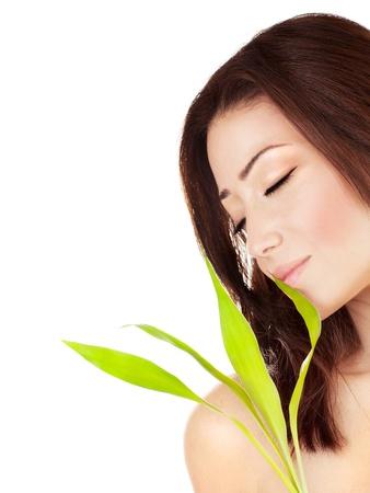 peluqueria y spa: Hermoso retrato de mujer joven, sosteniendo hojas de las plantas verdes, aisladas sobre fondo blanco con texto en blanco el espacio, la belleza y el concepto de spa