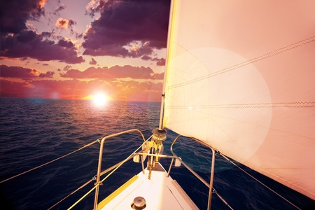 Romantic sunset and sail boat, dramatic sky with purple clouds and sun flare over calm sea, water sport, travel and freedom concept photo