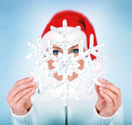 Snowflake in Santa girl hands, holding big flake, selective focus, winter holidays fun, celebrating Christmas photo