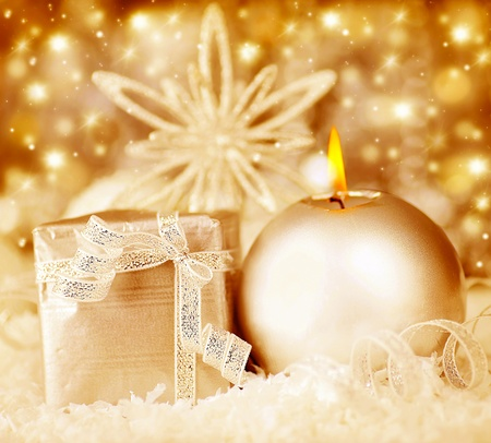 Golden Christmas decoration, warm glowing holiday background with candle and gift box, on dreamy bokeh lights, traditional ornament, wintertime celebrations  photo