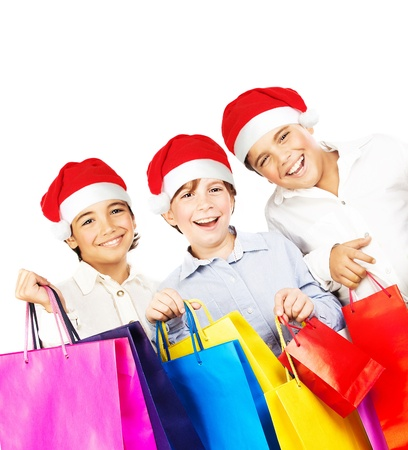 Happy Santa boys with gifts, kids carrying colorful shopping bags with Christmas presents isolated over white background, smiling preteen friends in red hats having fun, celebrating holidays photo