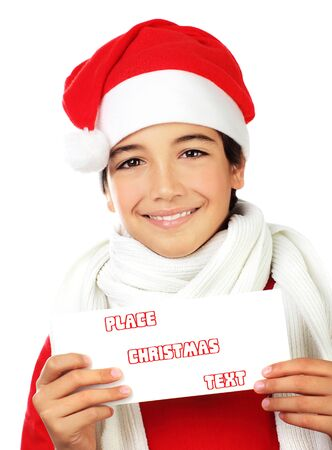 Happy Santa boy smiling, portrait of a cute teen holding blank card isolated on white backgroung, kid wearing red Christmas hat, winter holidays celebration photo