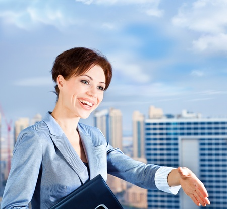 Successful businesswoman making a deal, young smart office worker, woman over blue sky & city background, handshake, business lifestyle concept photo