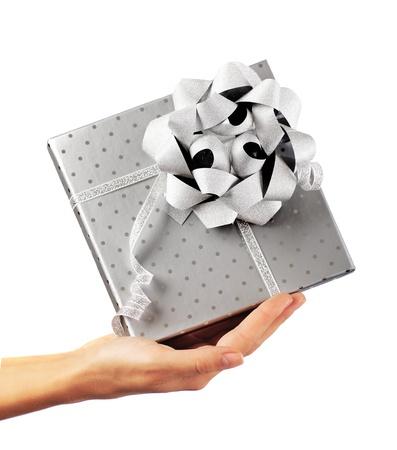 dar un regalo: Mano de mujer con hermosa caja de regalo de plata, lo que el concepto de regalo, fiestas de Navidad y la temporada de saludo, aisladas sobre fondo blanco