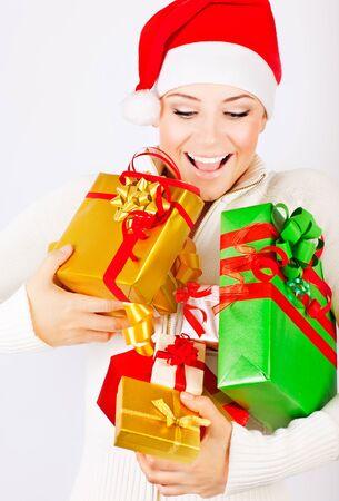 Happy Santa girl holding colorful Christmas gifts, Christmastime fun and joy, celebration of winter holidays, diversity of presents photo