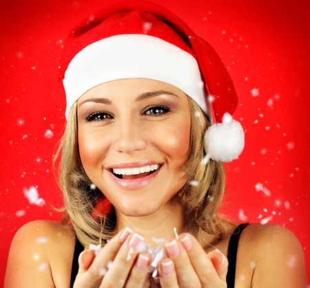 Portrait of pretty Santa girl laughing, isolated on red snowy winter holiday background photo