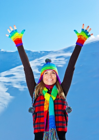 Happy cute girl playing in snow outdoor, looking up with hands up, beautiful woman smiling with raised arms to blue sky and nature, young teen female wearing colorful hat, Christmas winter holidays travel and vacation photo