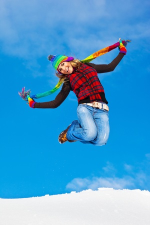 Happy girl jumping over blue sky background, teen outdoor winter activities, female having fun at Christmastime, woman wearing colorful clothes, freedom and success concept photo