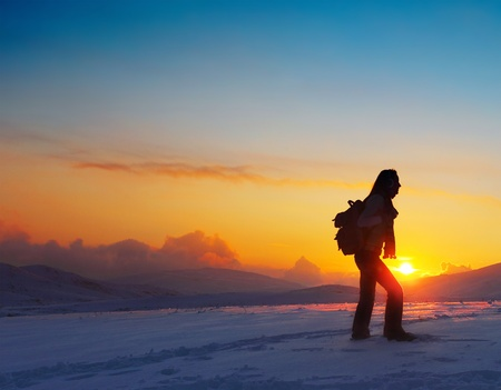 backpackers: Woman traveler hiking in winter mountains, trekking in wintertime cold snowy weather, girl silhouette over natural colorful sky with bright sunset and beautiful landscape, freedom concept