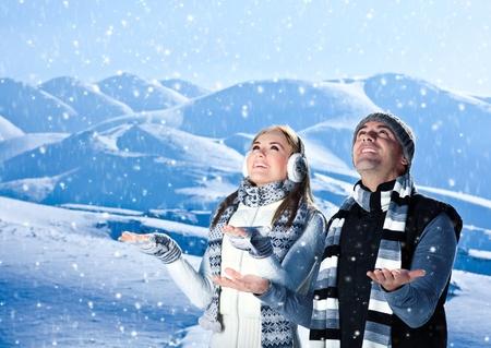 familia viaje: Pareja feliz jugando al aire libre en las monta�as de invierno, las personas naturales activos en fondo azul paisaje de invierno con nieve que cae, las vacaciones de Navidad de vacaciones