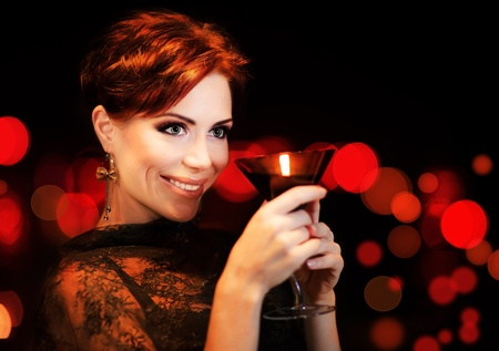 Beautiful female partying, celebrating holiday, portrait of a woman holding martini glass, girl over black background with red blur bokeh lights, luxury nightlife  photo