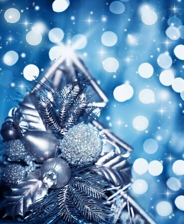 Beautiful silver Christmas tree decoration, blue shiny holiday background with blur bokeh glowing light and glitters, wintertime ornament, soft focus photo