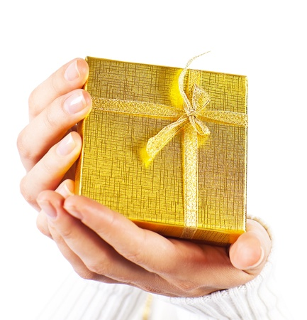Golden gift in womens hands, female holding present box, giving gift concept, christmas holidays and greeting season, isolated on white background photo