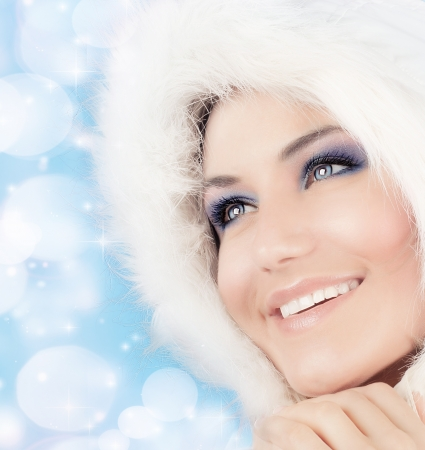 fur hood: Snow queen, beautiful woman in Christmas style makeup, female portrait over blue holiday background with shiny glowing glitters and bokeh lights
