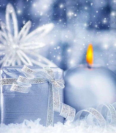 Winter holiday background with blue silver present gift box, candle ornament and Christmas snow decoration photo