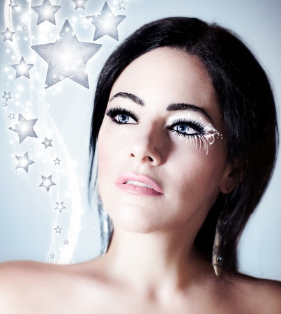 Snow queen, beautiful woman in Christmas style makeup, female portrait over blue holiday background with shiny glowing stars decoration   photo