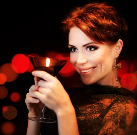 Beautiful female partying, celebrating holiday, portrait of a woman holding martini glass, girl over black background with red blur bokeh lights, luxury nightlife Stock Photo - 11599873