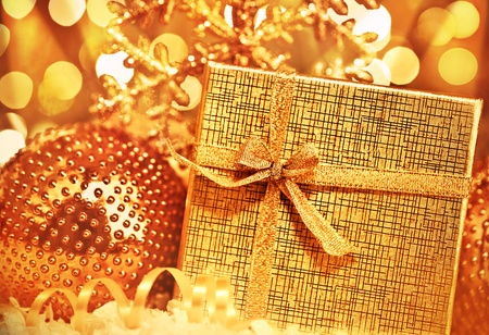 Golden gift box with baubles decorations, Christmas tree ornament for winter holidays, present with abstract bokeh shiny glowing blur lights background photo
