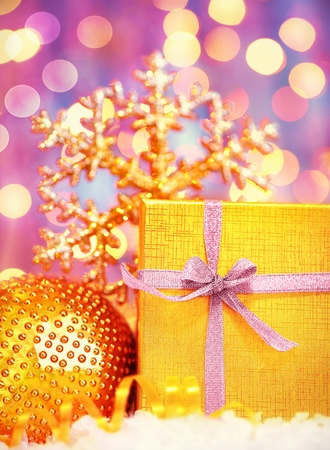 Golden gift box with baubles decorations, Christmas tree ornament for winter holidays, present with purple abstract bokeh shiny glowing blur lights background photo