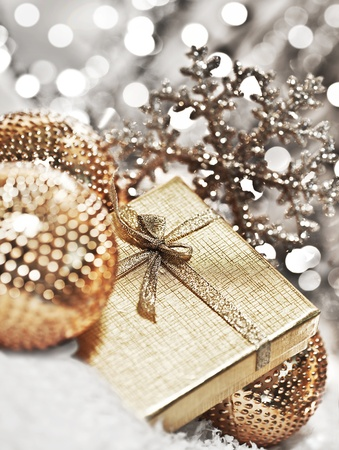 Silver gift box with baubles decorations, Christmas tree ornament for winter holidays, present with abstract bokeh shiny glowing blur lights background photo