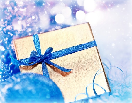 blue gift box: Golden blue gift box with baubles decorations, Christmas tree ornament for winter holidays, present with abstract bokeh shiny glowing blur lights background