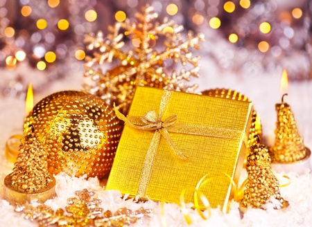 Golden gift box with baubles decorations and candles, Christmas tree ornament for winter holidays, present with abstract bokeh shiny glowing blur lights background photo