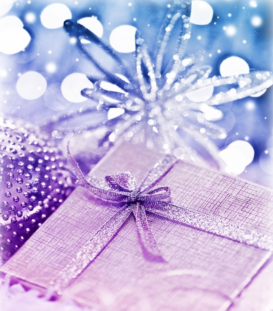 Purple blue gift box with baubles decorations, Christmas tree ornament for winter holidays, present with abstract bokeh shiny glowing blur lights background photo