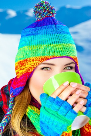 Beautiful girl drinking hot chocolate outdoor in winter, happy female teen wearing colorful hat, young pretty woman face, holding cup in hands photo