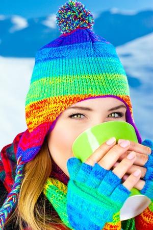 ropa de invierno: Hermosa niña de chocolate, bebida caliente al aire libre en invierno, feliz adolescente femenino con el sombrero de color, rostro joven y hermosa mujer, sosteniendo la taza en las manos Foto de archivo