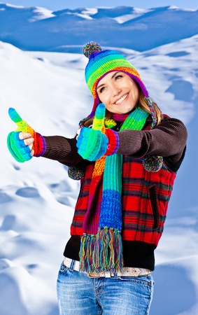 Colorful thumbs up of a happy smiling girl wearing winter clothes, beautiful female portrait, young pretty woman with natural snow background, winter fun outdoor, happy people concept photo
