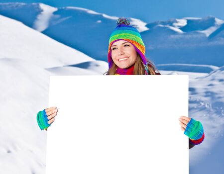 Happy girl holding white board, winter outdoor portrait, beautiful female teen in colorful hat, young pretty smiling woman holding blank paper card in hands, text space, copyspace photo