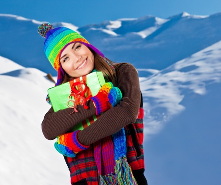 Happy girl with Christmas gift, winter outdoor portrait, beautiful female teen wearing colorful hat, young pretty smiling woman, holding present box in hands photo