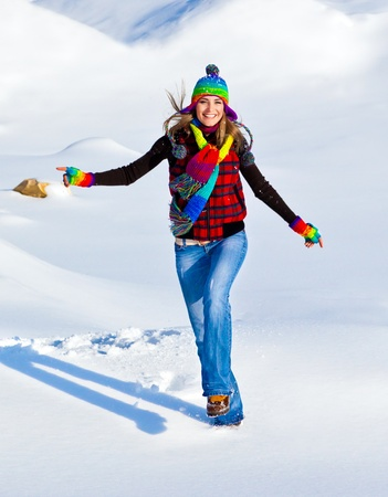 Happy girl running in the snow, teen outdoor winter activities, female having fun at Christmastime, woman wearing colorful clothes, freedom and nature joy concept