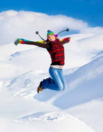 winter woman: Happy girl jumping over blue sky and snow background, teen outdoor winter activities, female having fun at Christmastime, woman wearing colorful clothes, freedom and success concept
