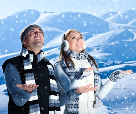 winter clothes: Happy couple playing outdoor at winter mountains, active people over natural blue wintertime landscape background with falling snow, Christmas vacation holidays