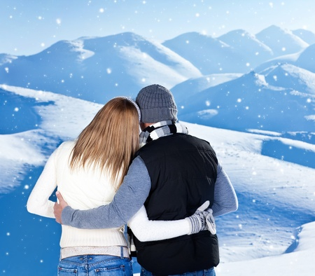 Happy couple hugging outdoor at winter mountains, rear view, two in love over natural blue wintertime landscape background with falling snow, romantic Christmas vacation holidays