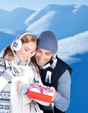 Happy couple with gift, people outdoor at winter snow mountains, young man giving present to beautiful woman, Christmas vacation holidays, love concept photo