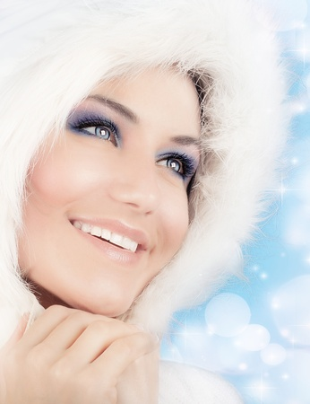Snow queen, beautiful woman in Christmas style makeup, female portrait over blue holiday background with shiny glowing glitters and bokeh lights photo