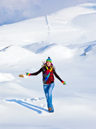 Happy girl running in the snow, teen outdoor winter activities, female having fun at Christmastime, woman wearing colorful clothes, freedom and nature joy concept photo